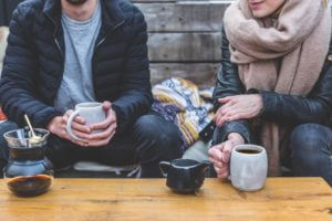 couple drinking coffee outside in chilly weather
