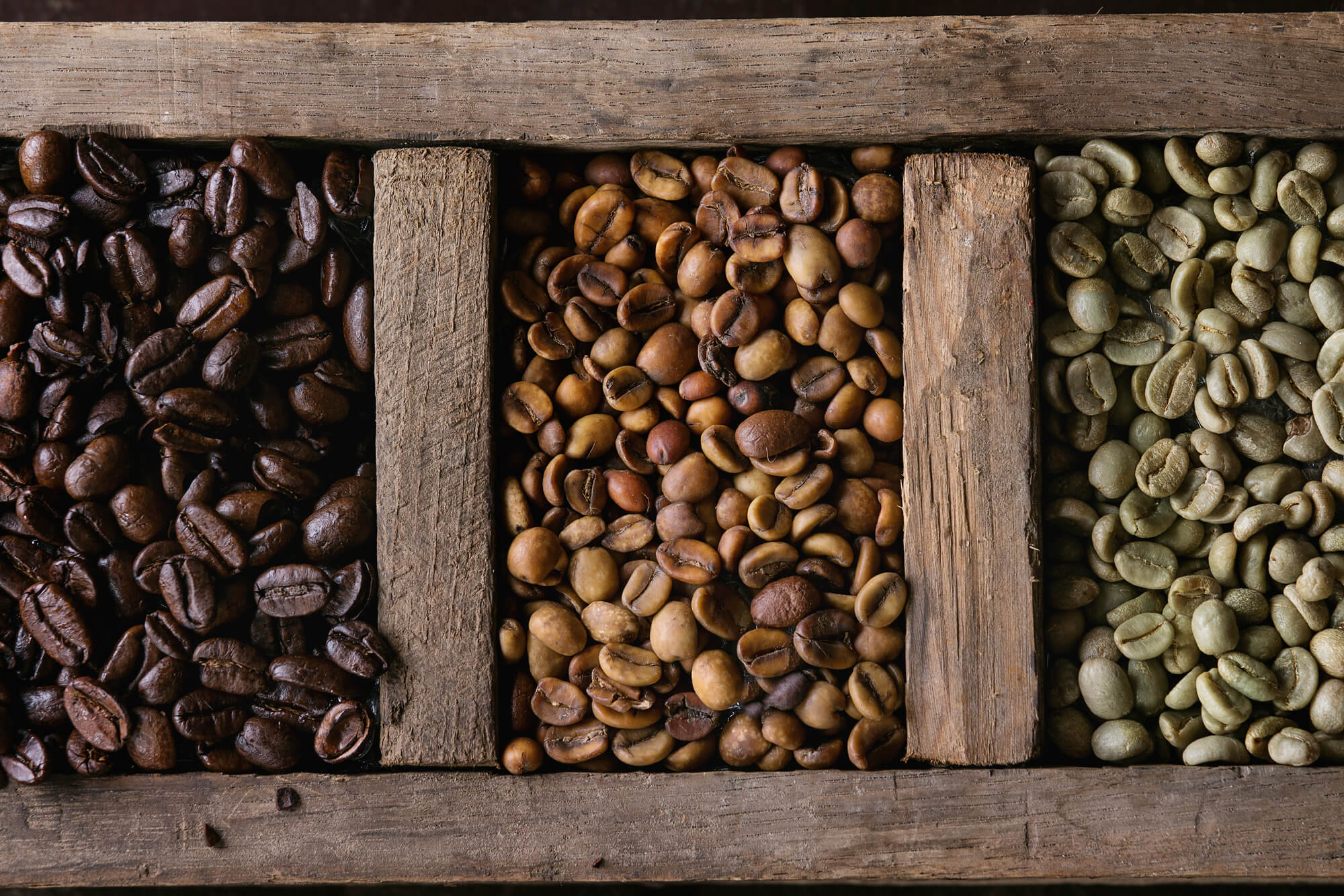 Green and Brown Decaf Unroasted and Black Roasted Coffee Beans in Old Wooden Box.